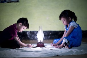 Village Girl and boy studying in lighting lamp