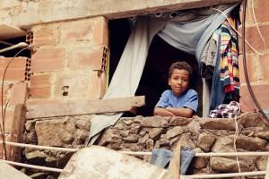 A young Brazilian boy looks out his bedroom window in the Santa Marta favela of Rio de Janeiro.