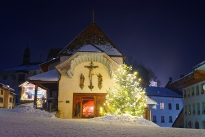 Beautifully decorated and illuminated Christmas fir tree in front of the church in Gruyere, Switzerland
