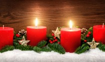 Low-key studio shot of elegant advent decoration with fir branches on snow and tow burning red candles, dark wood background