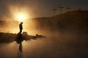 Dramatic religious photo illustration of Good Friday and Easter Sunday Morning reflecting a prayerful moment of silence with a silhoutted person bowing his head, a warm sunrise rises over a foggy lake, and three crosses on a hill reflected in the water as well.