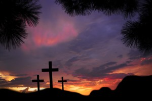 Easter.  The crucifixion with three crosses in silhouette stand silently on a landscape scene with a dramatic sky in purple hues.  Christianity, religious themes. Copyspace.