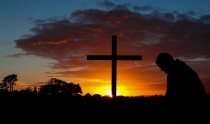 Man in pray before a cross at sunrise.