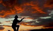 A man worshiping God at a spectacular sunset after a storm