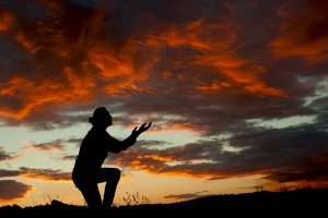 A man worshiping God at a spectacular sunset after a storm