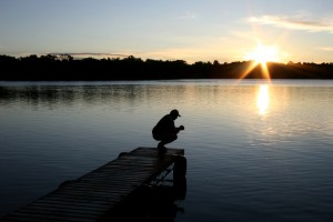 An unrecognizable Caucasian man kneeling and praying on a dock at a lake. Man is folding his hands and is in silhouette. One person is in the image. Sun flare and beautiful sunrise highlight the Christianity themed image. Man is in his 30s and is alone spending time with God.