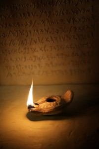 Oil Lamp with Ancient Inscription in Background