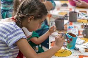 Timisoara, Romania - June 1, 2016: Girl who paints a ceramic bowl. Workshop organized by the City Hall Timisoara with the occasion of the International children Day.