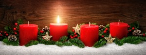 Low-key studio shot of elegant advent decoration with fir branches on snow and one burning red candle, dark wood background