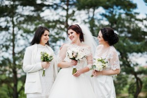 Pretty bride with bridesmaids on white dresses with bouquets on hands at wedding day.