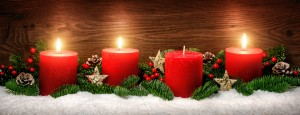 Low-key studio shot of elegant advent decoration with fir branches on snow and three burning red candles, dark wood background