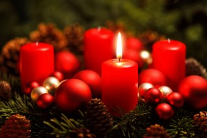 Low-key studio shot of a nice advent wreath with baubles and one burning red candle