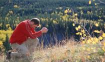 A man prays in a beautiful outdoor scene.